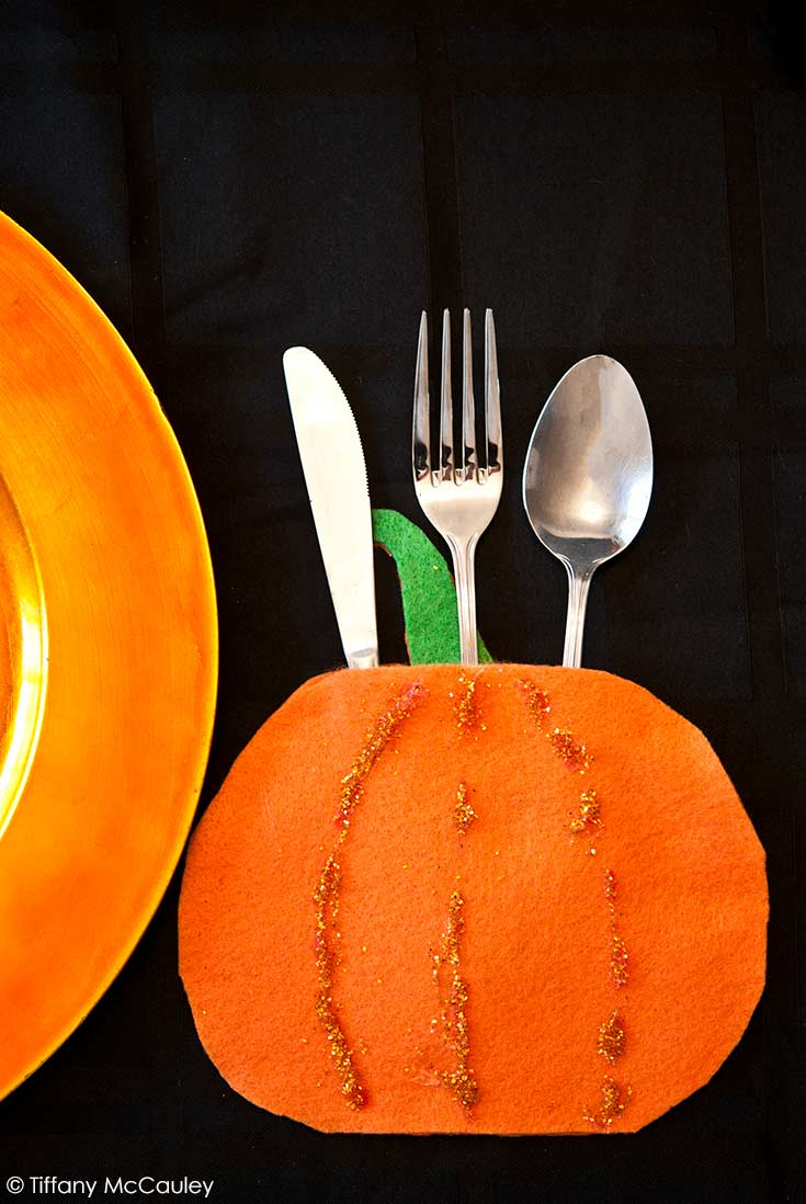 One of these Halloween Silverware Holders sits with silverware in it on a black table cloth. An orange platter sites next to it.