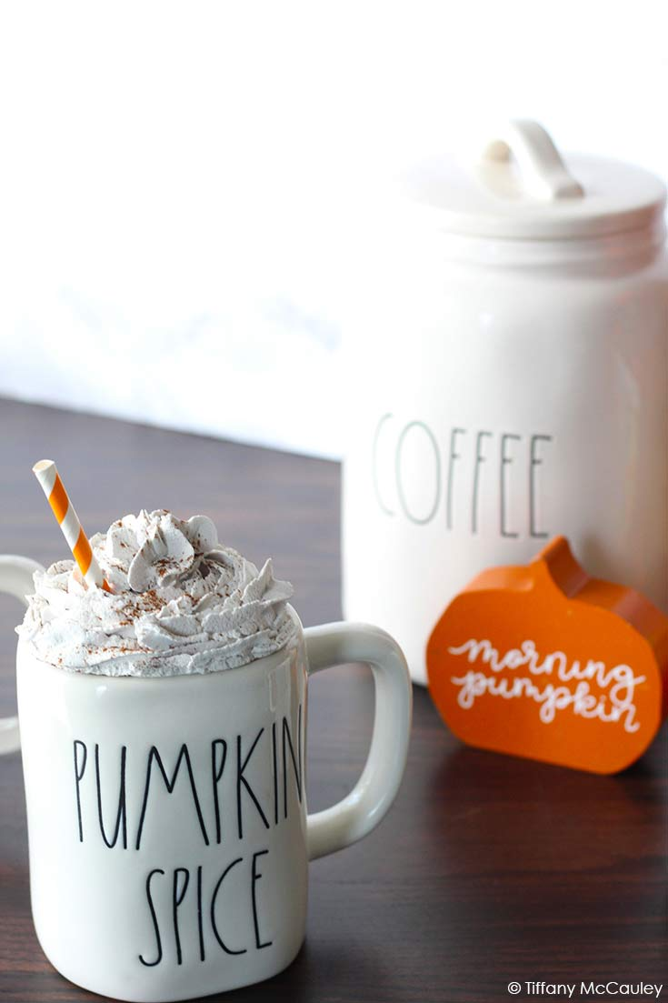 A mug with a mug topper sits to the left and a coffee canister to the back and right. An orange pumpkin sits in front of the coffee canister.