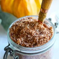 A jar of these Pumpkin Spice Bath Salts sits with a spoon in it, ready to use in your next, relaxing bath.