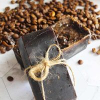 Two bars of this Pumpkin Spice Latte Soap Recipe sit in a pile of coffee beans, wrapped in twine.