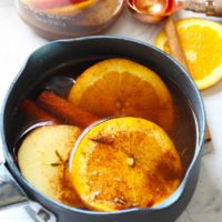 A pot filled with this Fall Stovetop Potpourri sits on a countertop, ready to move to the stove. You can see slices of orange and apple as well as cinnamon sticks.