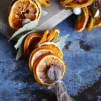 A dried orange garland lays across a dark counter top and cutting board.