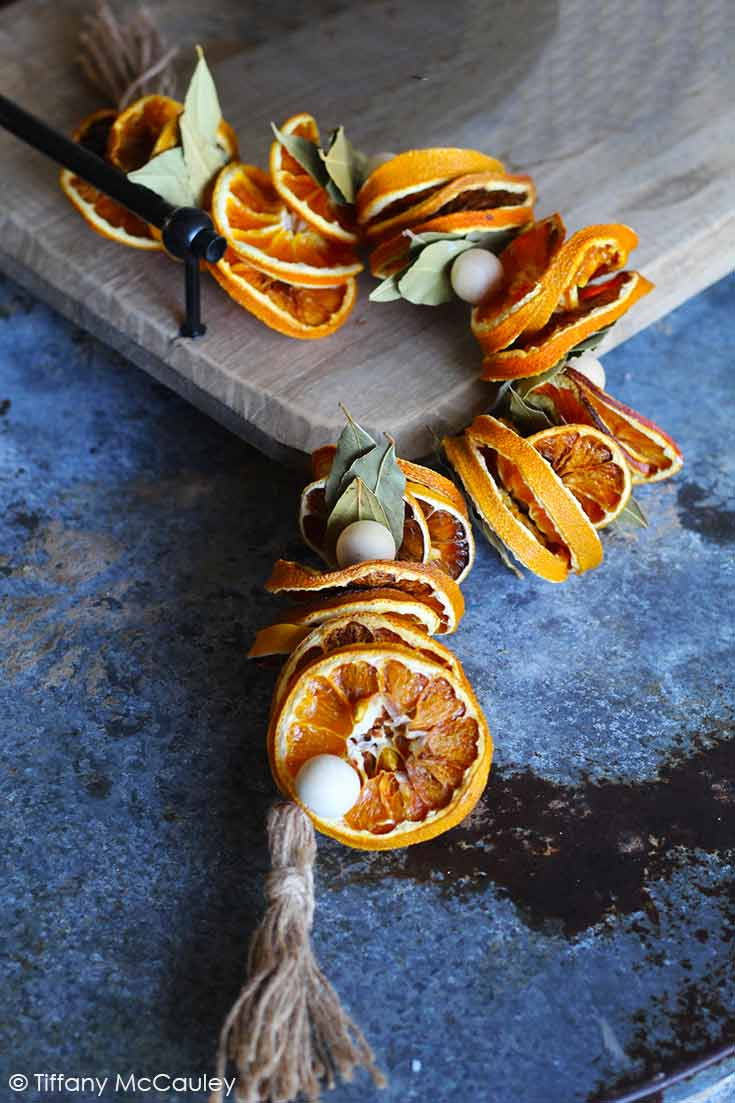 A dried orange garland sits on a counter, waiting to be hung.