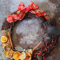 A beautiful citrus wreath with citrus slices, bay leaves and red berries to hang on your door or in your house.