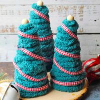 Three Yarn Christmas Trees sit on a wooden base as a beautiful decoration.