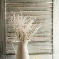 Tips and tricks for How To Get That Farmhouse Look. A pitcher sits in front of a white-washed shutter with a small white pumpkin next to it.