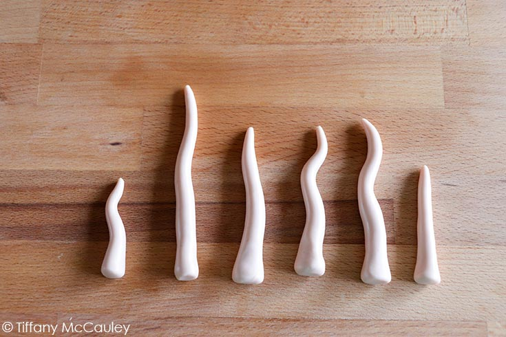The finished mushroom stems lined up in a row on a wooden surface.