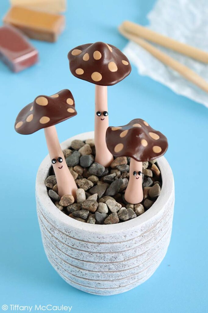 Three Polymer Clay Mushrooms in a small, white pot.